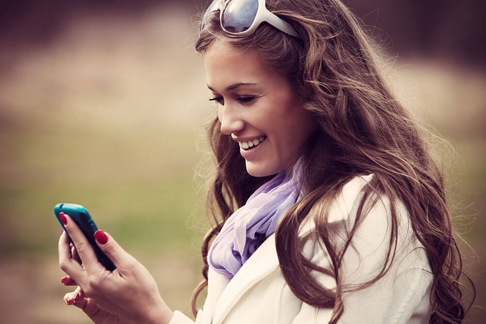 Woman looking at smartphone and smiling