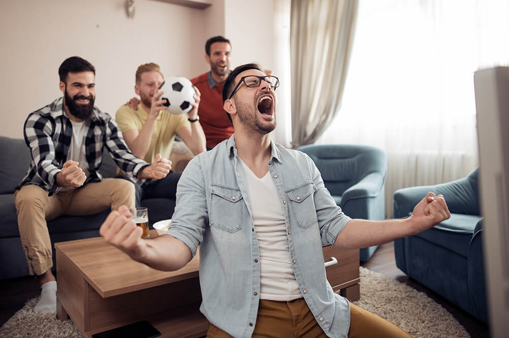Four men celebrate their soccer team scoring as they watch on TV in the front room.