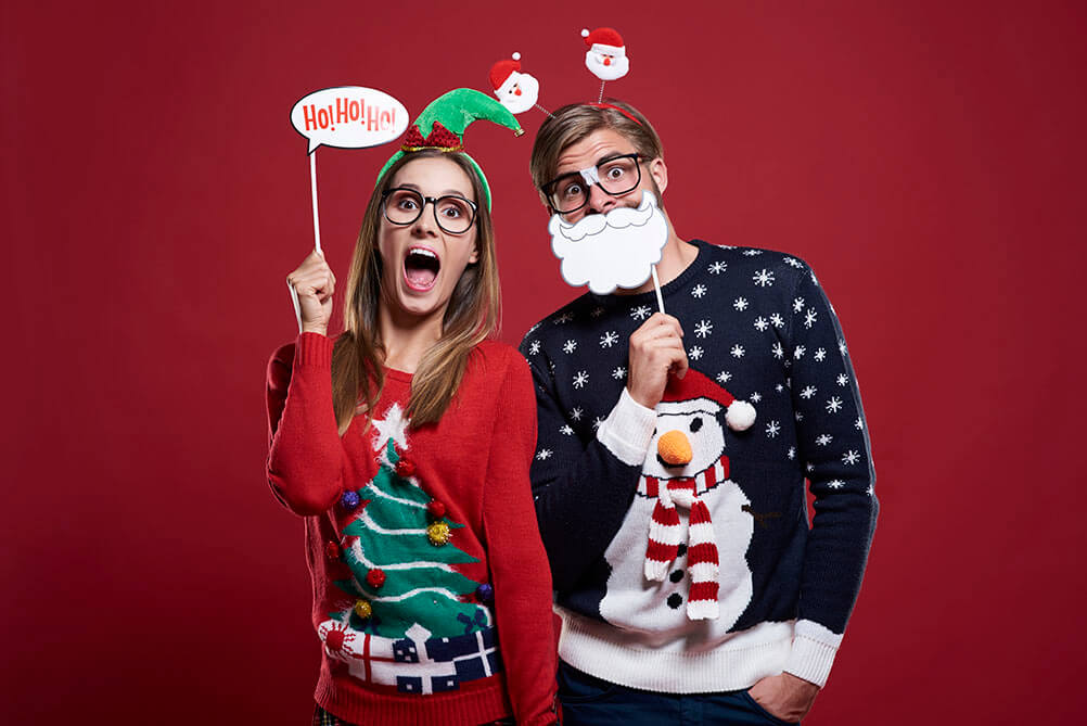 Couple dressed up in Christmas outfits against a red background