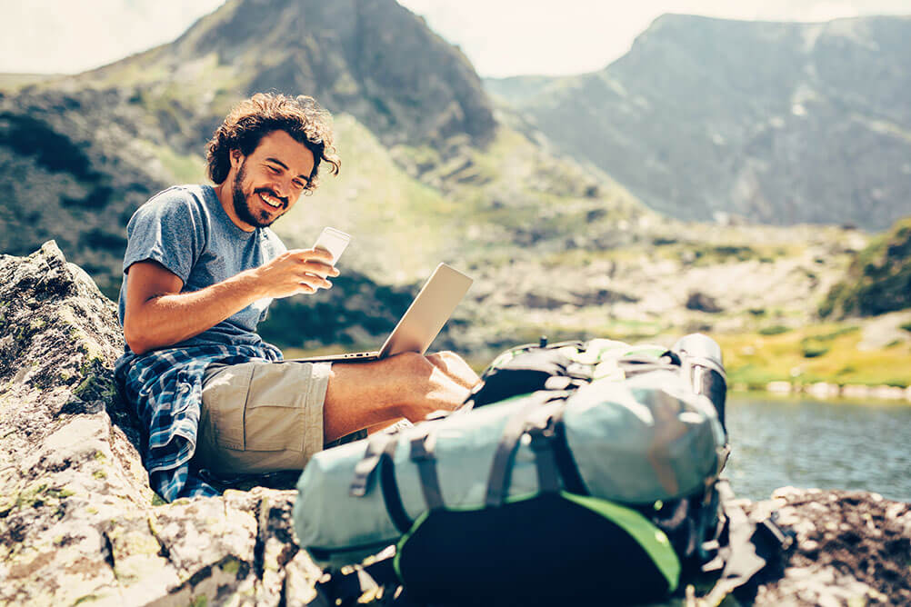 A man checks his laptop and phone while working remotely from a mountainous region