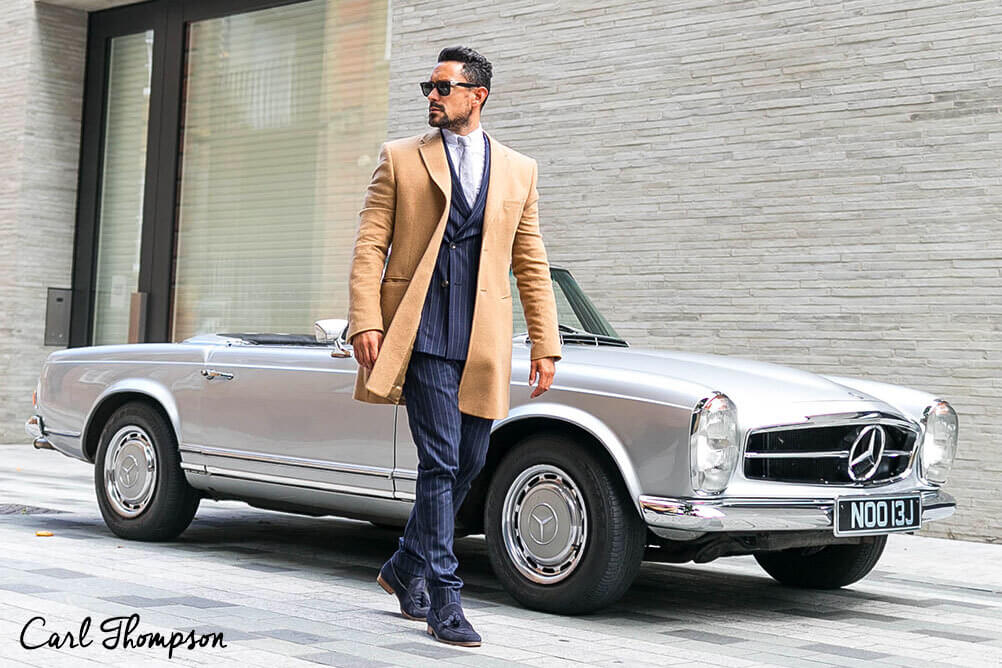 Carl Thompson dresses like a rich man standing in front of an expensive car