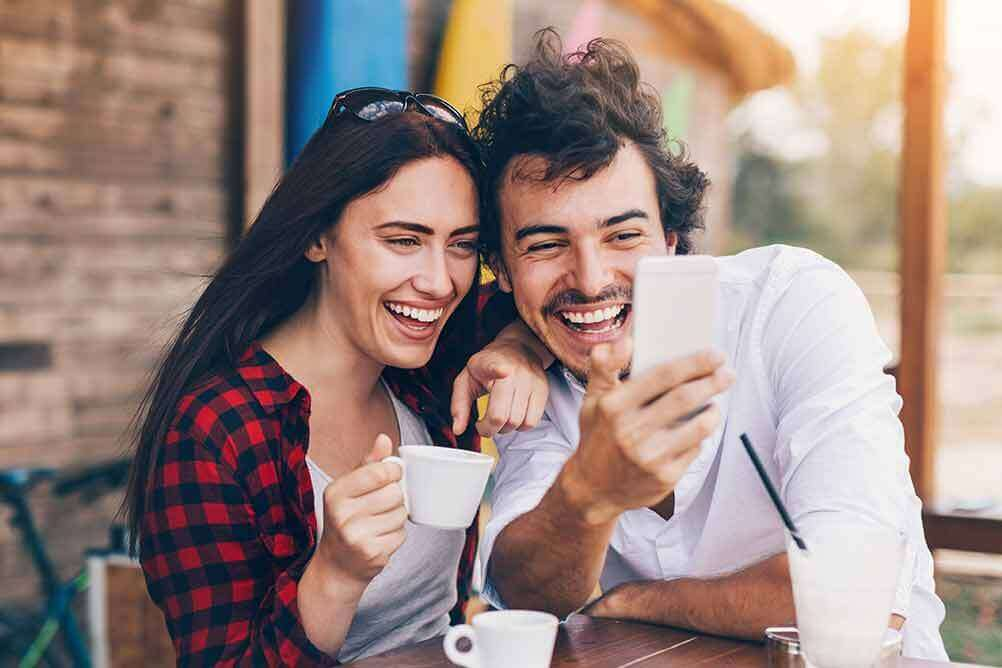 Laughing couple betting on EuroJackpot online with their smartphone